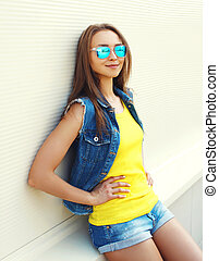 Portrait fashion pretty smiling woman wearing a sunglasses and jeans clothes in the city