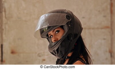 side view independent woman in motorcycle helmet turns to the camera slow motion