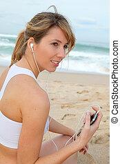 portrait, femme, plage, exercisme, écouteurs