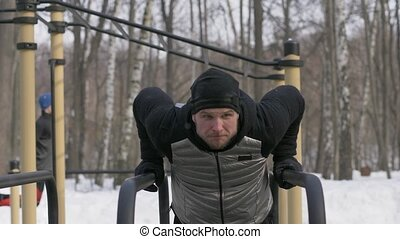Portrait fitness man doing push ups exercise on bar on...
