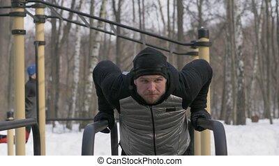 Portrait fitness man doing push ups exercise on bar on...