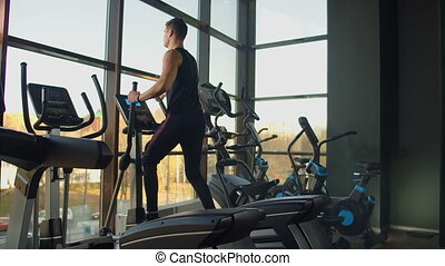 Portrait fitness man warm up before training on elliptical cross trainer in gym club. Close-up male training cardio exercise on cross trainer in fitness.