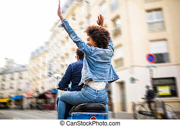 behind of happy young african american woman sitting on back of scooter driving through city streets with arms raised