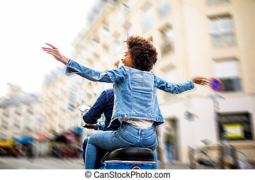 behind of young african american woman sitting on back of scooter driving through city streets with arms raised