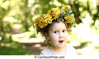 Portrait Funny baby girl with wreath of yellow tansy flower on her head. Close-up. Child looking at the camera, in the forest.