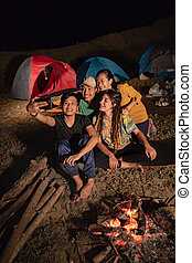 portrait group of friends camping, take a picture around camp fi