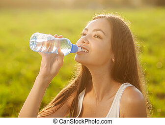 Portrait half face of young woman drink water bottle at summer green park