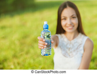 Portrait half face of young woman holding water bottle at summer green park
