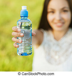 Portrait half face of young woman holding water bottle at summer