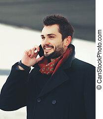 Portrait handsome bearded smiling man talking on smartphone walking outdoors