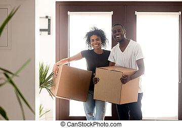 Portrait happy African American couple on moving day in new house