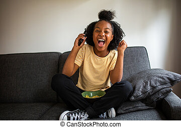 happy african american girl sitting on sofa with tv remote control