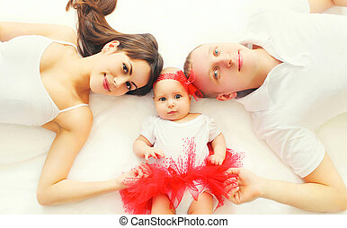 Portrait happy family mother, father and baby lying on the bed at home, top view