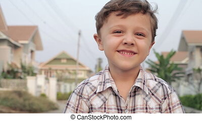 happy little boy playing near a house