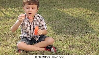 Portrait happy little boy sitting in the park