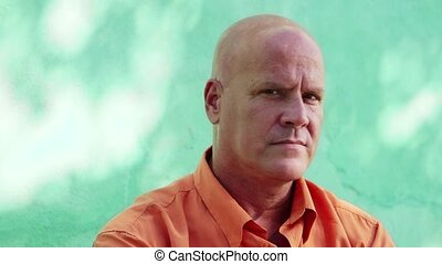 Portrait of mature caucasian man with orange shirt sitting in park and looking at camera with happy expression. 5 of 11