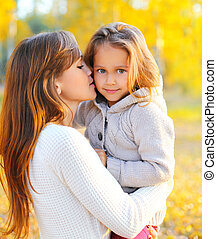Portrait happy mother kissing child in warm sunny autumn day