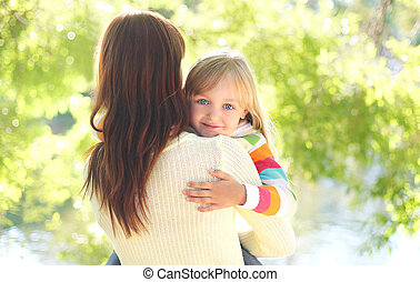 Portrait happy smiling child hugging mother in summer day