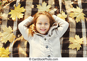 Portrait happy smiling child lying on plaid with yellow maple leafs in autumn day