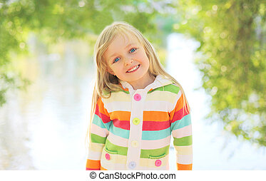 Portrait happy smiling child outdoors in summer day