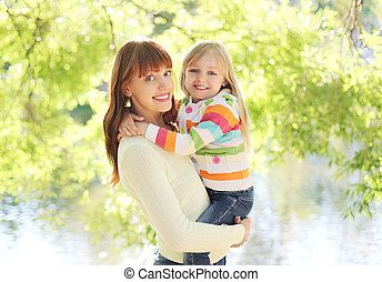 Portrait happy smiling mother and child hugging in summer day