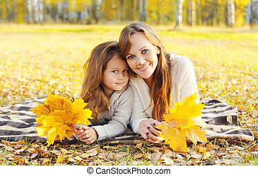Portrait happy smiling mother and child together with yellow maple leafs in autumn day