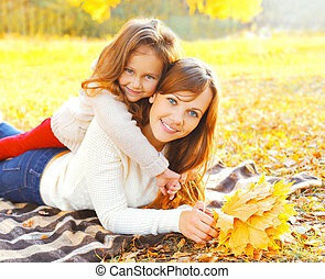 Portrait happy smiling mother and child together with yellow maple leafs lying on the plaid in warm sunny autumn day