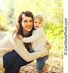 Portrait happy smiling mother and child walking in autumn day