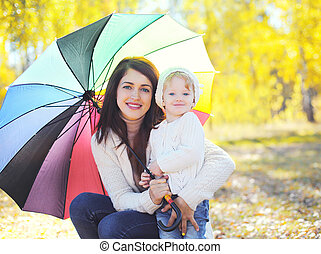 Portrait happy smiling mother and child with umbrella walking in autumn park