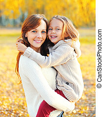 Portrait happy smiling mother hugging child in warm sunny autumn day