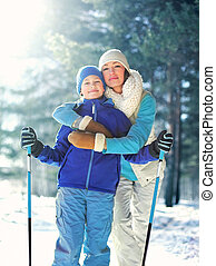 Portrait happy smiling mother hugging child with ski in winter cold forest