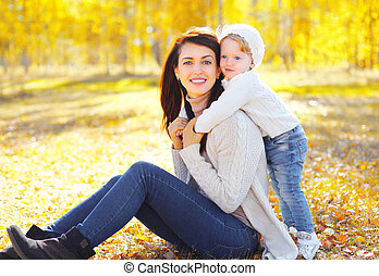 Portrait happy smiling mother playing with child in warm sunny autumn day