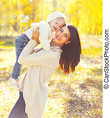 Portrait happy smiling mother with child having fun playing in warm sunny autumn day