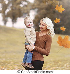 Portrait happy smiling mother with her child on a autumn day, flying maple leaves