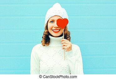 Portrait happy smiling young woman holds lollipop stick heart shape in knitted white hat, sweater on blue background
