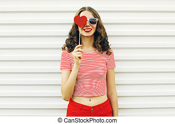 Portrait happy smiling young woman with red heart shaped lollipop on white wall background