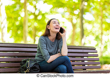 happy woman sitting on park bench talking with cellphone