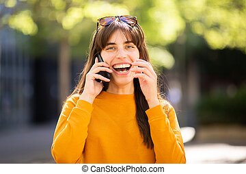 happy woman talking with cellphone in park and laughing