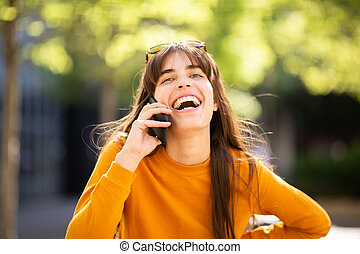 happy woman talking with cellphone in park