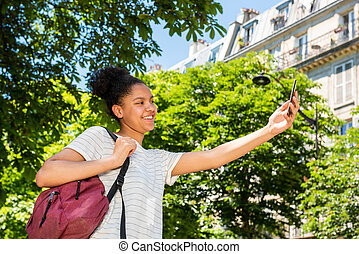 happy young african american school girl with bag and mobile phone taking selfie outside