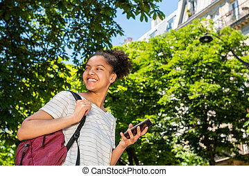 happy young african american school girl with bag and mobile phone walking outside