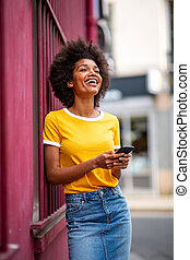 happy young african american woman holding cellphone outside in city