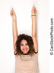 happy young african american woman with arms raised and pointing up