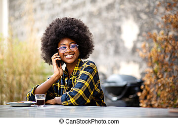 happy young black woman sitting outside talking with cellphone