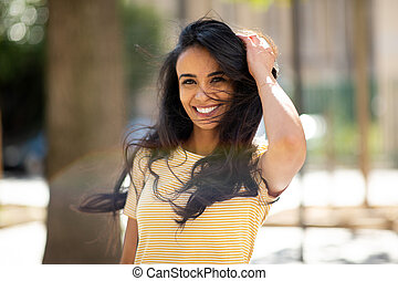happy young hispanic woman smiling with hand in hair