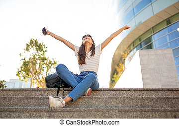 happy young woman sitting on steps with arms raised in sky