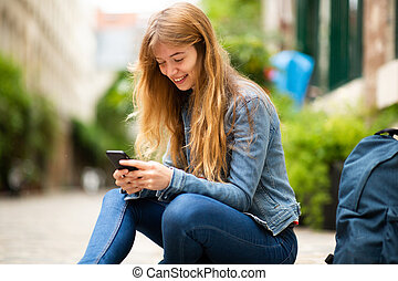happy young woman sitting outside with mobile phone