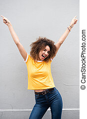 happy young woman with arms raised and pointing fingers up