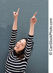 happy young woman with arms raised pointing fingers up against gray background