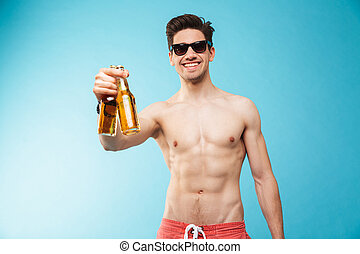Portrait if a smiling shirtless man showing beer bottle